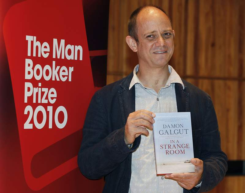 FILE - In this Sunday, Oct. 10, 2010 file photo, Damon Galgut with his book 'In a Strange Room' takes part in a photocall on the stage of the Royal Festival Hal in London. Novels that explore historical injustices, the nature of consciousness and the dizzying impact of the internet are among six finalists for the prestigious Booker Prize for fiction. Contenders include Sri Lankan author Anuk Arudpragasams A Passage North, South African writer Damon Galguts The Promise and British/Somali writer Nadifa Mohameds The Fortune Men. The winner will be crowned Nov. 3, 2021 in London. (AP Photo/Kirsty Wigglesworth, file)
