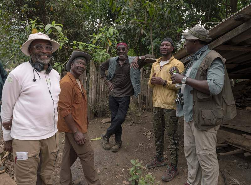 """This image released by Netflix shows, from left, filmmaker Spike Lee, from left, with Clarke Peters, Delroy Lindo, Jonathan Majors and Norm Lewis on the set of """"Da 5 Bloods."""" (David Lee/Netflix via AP)"""