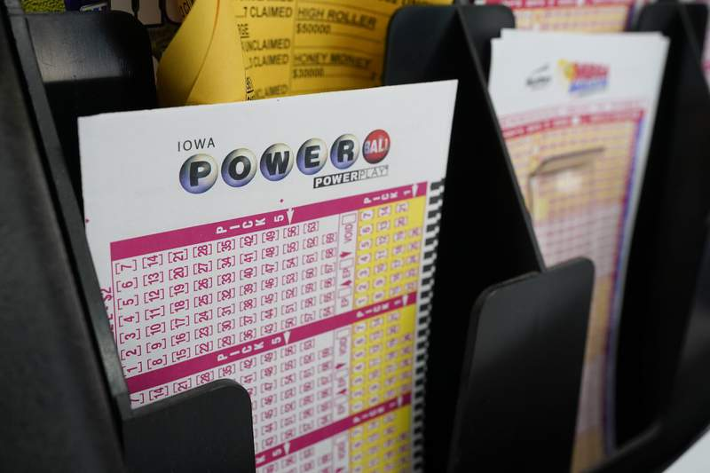 FILE - In this Jan. 12, 2021 file photo, blank forms for the Powerball lottery sit in a bin at a local grocery store, in Des Moines, Iowa. (AP Photo/Charlie Neibergall)