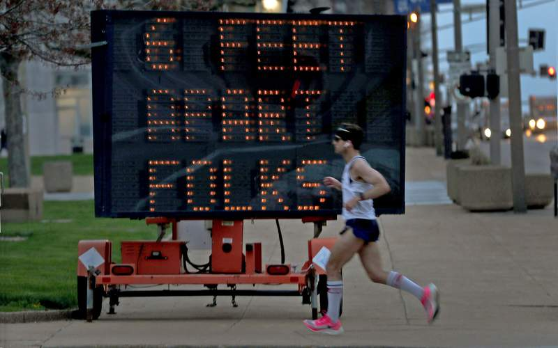A person jogs past a sign encouraging social distancing Thursday. Exercise is one of the allowed exceptions to most stay-at-home and shelter-in-place orders in place to slow the spread of the coronavirus.