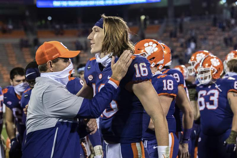 Clemson head coach Dabo Swinney, left, pats Clemson quarterback Trevor Lawrence (16) on the shoulder following their win over Pittsburgh in an NCAA college football game in Clemson, S.C., Saturday, Nov. 28, 2020. (Ken Ruinard/The Independent-Mail via AP, Pool)