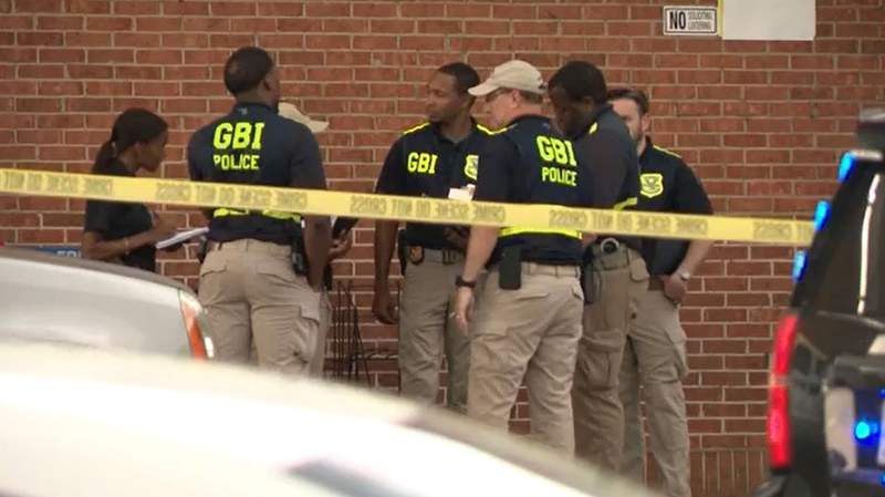 GBI assists DeKalb County sheriff's investigators outside the Big Bear Supermarket after a clerk was shot and killed by a gunman who also shot a reserve deputy, who return gunfire and wounded the suspect.