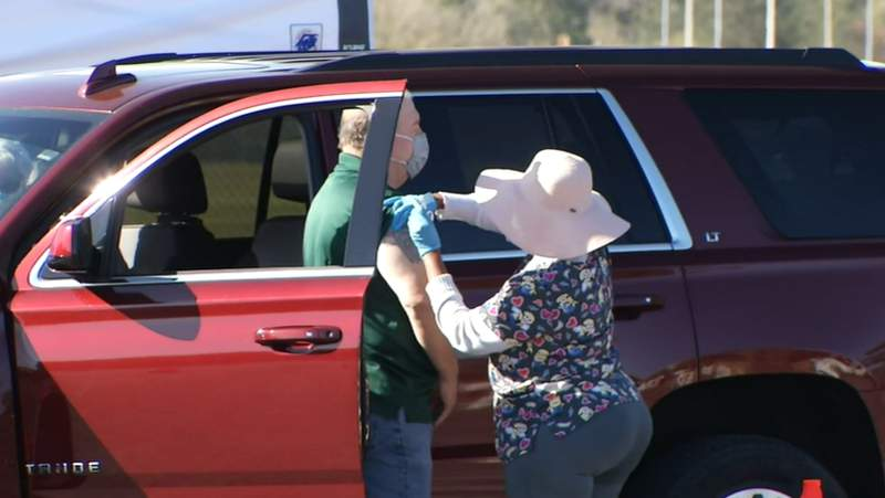 Health worker administers a coronavirus vaccine at a drive-thru site in Lake City.