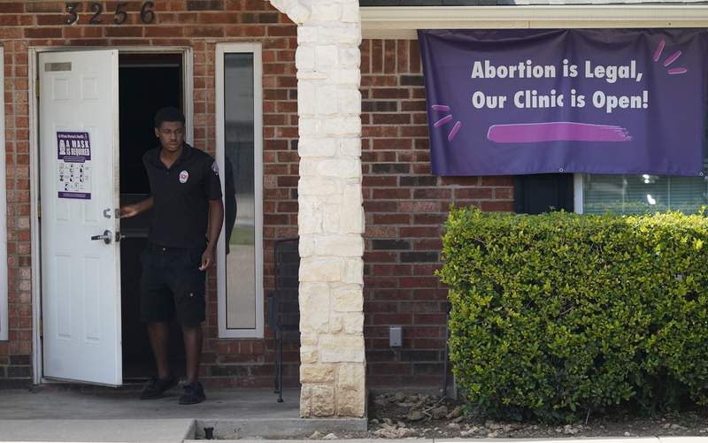 FILE - In this Wednesday, Sept. 1, 2021 file photo, a security guard opens the door to the Whole Women's Health Clinic in Fort Worth, Texas. A Texas law banning most abortions in the state took effect at midnight. (AP Photo/LM Otero, File)