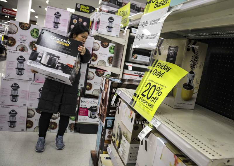 FILE - In this Nov. 29, 2019 file photo, a shopper carries a crockpot during Target's Black Friday sale, in the Borough of New York. The National Retail Federation, the nations largest retail group,  expects that holiday sales could actually exceed growth seen in prior seasons despite the uncertainty surrounding the pandemic. (AP Photo/Bebeto Matthews, File)