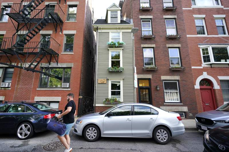 """FILE In this Aug. 13, 2021 file photograph, a man walks by Boston's famous Skinny House, at center, after it was listed for sale for $1.2 million. The sale of the home was closed Thursday Sept. 16, 2021 for $1.25 million, according to Zillow. The home """"received multiple offers and went under agreement for over list price in less than one week,"""" real estate agency CL Properties posted on Facebook.   (AP Photo/Elise Amendola, File)"""