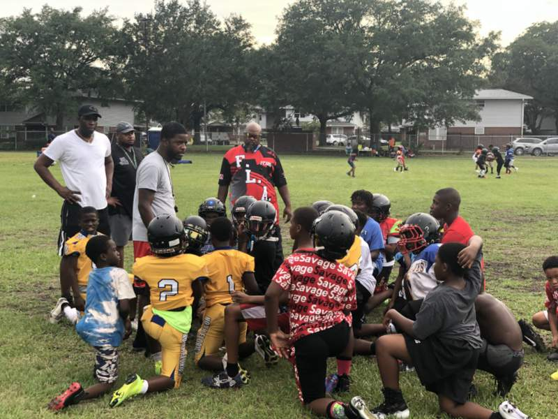 Coaches of the FLA Vikings talk to a group of players during a practice on Tuesday night.