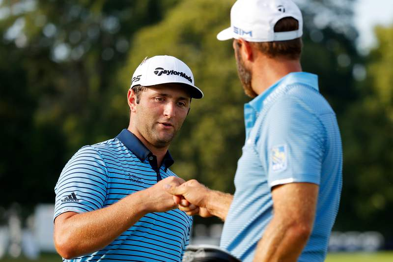 ATLANTA, GEORGIA - SEPTEMBER 04: Jon Rahm of Spain and Dustin Johnson of the United States bump fists on the 18th green during the first round of the TOUR Championship at East Lake Golf Club on September 04, 2020 in Atlanta, Georgia. (Photo by Kevin C. Cox/Getty Images)
