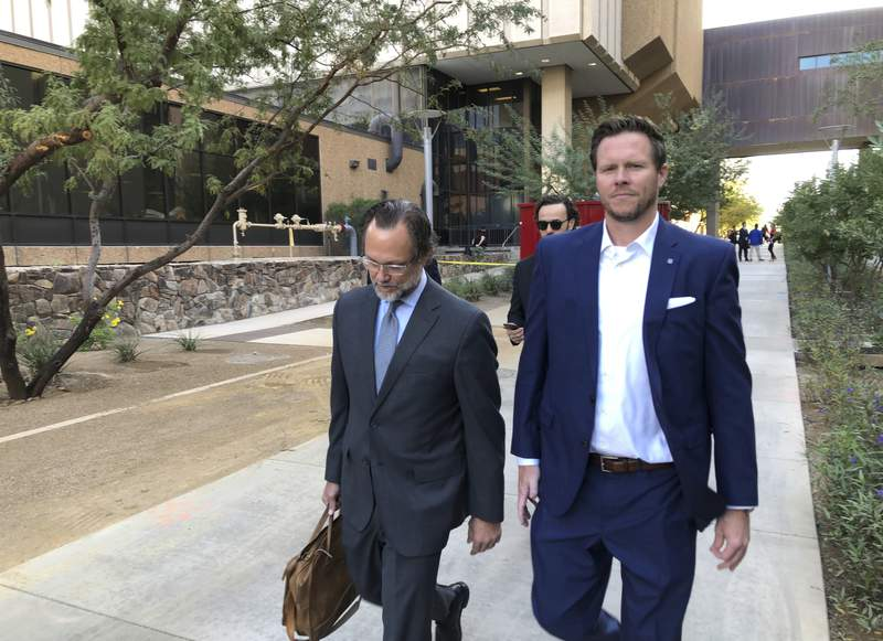 FILE - In this Nov. 5, 2019, file photo, then-Maricopa County Assessor Paul Petersen, right, and his attorney, Kurt Altman, leave a court hearing in Phoenix. The former Arizona politician could serve up to 15 years in prison for operating an illegal adoption scheme involving women from the Marshall Islands after he was given his third sentence Wednesday, April 21, 2021, in Utah. Petersen had already been ordered to serve 11 years in prison in Arizona and Arkansas.(AP Photo/Jacques Billeaud, File)