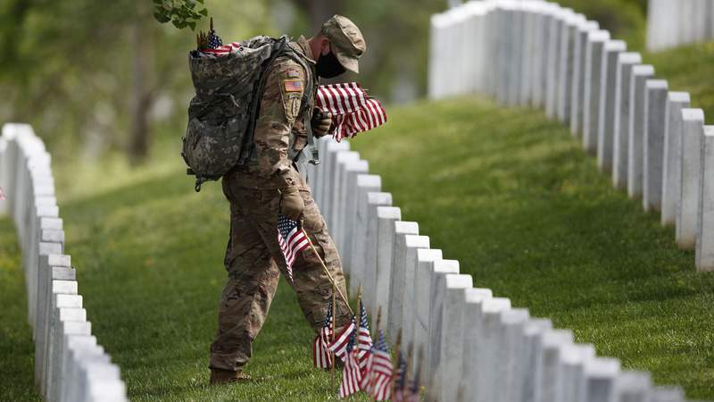 Masked soldier places flags on graves at Arlington National Cemetery.