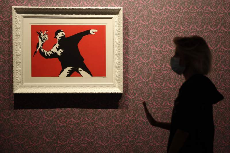 """A worker walks past """"Love Is in the Air"""", a screen print on paper, by British artist Banksy, a day before the unveiling of an exhibition in Rome, Monday, Sept. 7, 2020. The exhibition opens on Sept. 8 and runs until April 11, 2021. (AP Photo/Alessandra Tarantino)"""