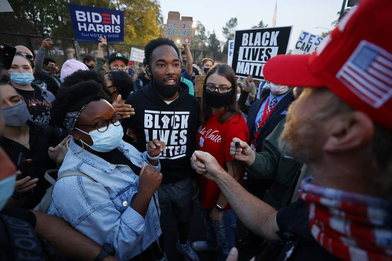 FILE - In this Oct. 7, 2020, file photo, supporters for former Vice President Joe Biden and Black Lives Matter, clash with President Donald Trump supporters prior to the vice presidential debate in Salt Lake City. Several years since its founding, BLM has evolved well beyond the initial aspirations of its early supporters. (AP Photo/Jeff Swinger)