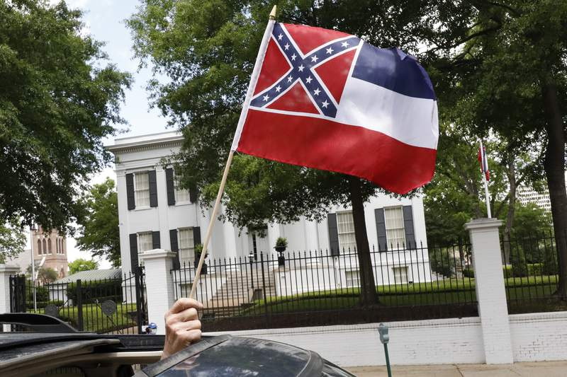 """In this April 25, 2020 photograph, a small Mississippi state flag is held by a participant during a drive-by """"re-open Mississippi"""" protest past the Governor's Mansion, in the background, in Jackson, Miss. This current flag has in the canton portion of the banner the design of the Civil War-era Confederate battle flag, that has been the center of a long-simmering debate about its removal or replacement. (AP Photo/Rogelio V. Solis)"""