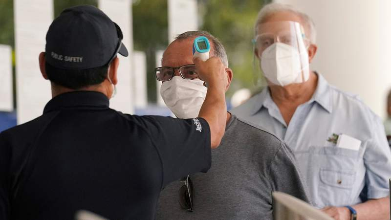 Florida seniors have their temperatures taken before receiving the second dose of the Pfizer COVID-19 vaccine at Jackson Health System in Miami.