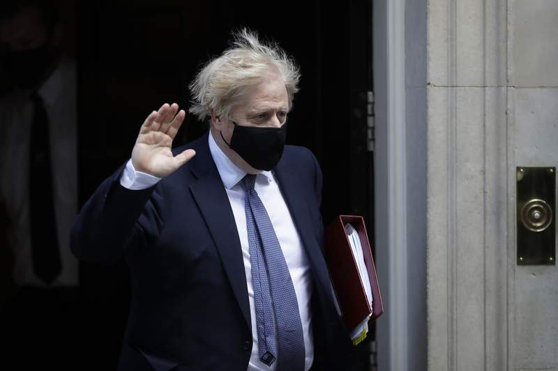 FILE - In this file photo dated Wednesday, May 19, 2021, wearing a face covering British Prime Minister Boris Johnson waves at the media as he leaves 10 Downing Street in London. An independent report Tuesday May 25, 2021, says British Prime Minister Boris Johnson helped create an impression that his Conservative Party is insensitive to Muslims.(AP Photo/Matt Dunham, FILE)