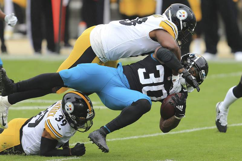 Jacksonville Jaguars running back James Robinson (30) is brought down by Pittsburgh Steelers linebacker Vince Williams, top, and safety Minkah Fitzpatrick (39) during the first half of an NFL football game, Sunday, Nov. 22, 2020, in Jacksonville, Fla. (AP Photo/Matt Stamey)