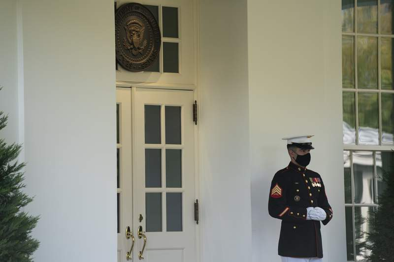 A Marine is posted outside the West Wing of the White House, signifying the President is in the Oval Office, Friday, Oct. 9, 2020, in Washington. (AP Photo/Evan Vucci)