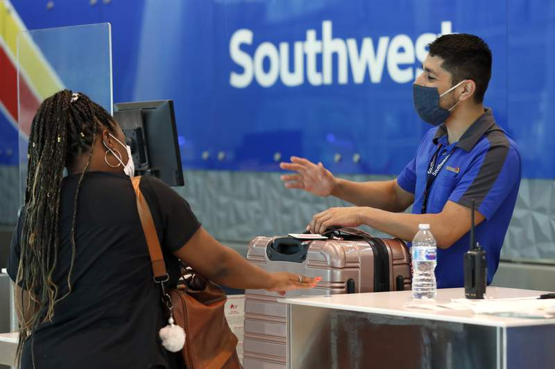FILE - In this June 24, 2020 file photo, Southwest Airlines employee Oscar Gonzalez, right, assists a passenger at the ticket counter at Love Field in Dallas. Southwest Airlines cautioned Thursday, Nov. 12, 2020 that the tenuous recovery in air travel could be fading as coronavirus cases spike across the United States. The nations fourth-biggest airline said after a modest rise in leisure-travel bookings from August through October, it now sees a slowdown in improving revenue trends for November and December. (AP Photo/Tony Gutierrez, File)