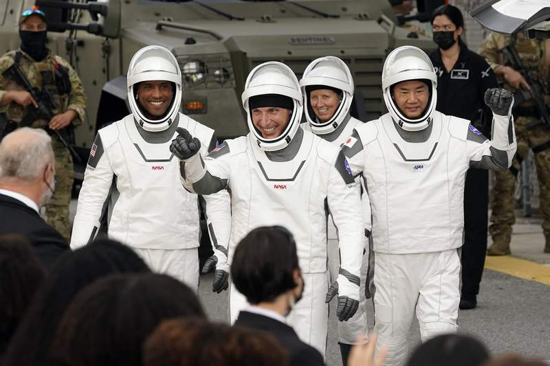 Astronauts, from left, Victor Glover, Michael Hopkins, Shannon Walker, and Japan Aerospace Exploration Agency astronaut Soichi Noguchi wave to family members as they leave the Operations and Checkout Building for a trip to Launch Pad 39-A and planned liftoff on a SpaceX Falcon 9 rocket with the Crew Dragon capsule on a six-month mission to the International Space Station Sunday, Nov. 15, 2020, at the Kennedy Space Center in Cape Canaveral, Fla. (AP Photo/John Raoux)