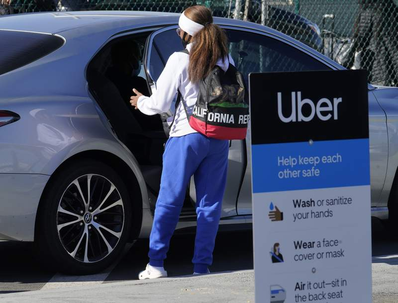 FILE - In this Nov. 13, 2020 file photo, a traveler rides in the back of an Uber vehicle at Los Angeles International Airport in Los Angeles.   Uber saw record demand in the first quarter, Wednesday May 5, 2021,  as its food delivery business remained strong ease even as lockdowns ended and more customers hailed rides(AP Photo/Damian Dovarganes, File)