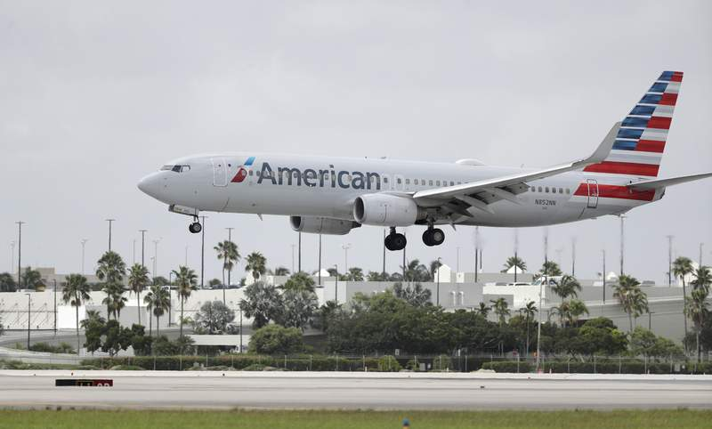 FILE - In this Monday, July 27, 2020, file photo, An American Airlines Boeing 737-823 lands at Miami International Airport in Miami. American Airlines is telling some flight attendants to cut short their leaves of absence and come back to work. The airline said Thursday, July 15,  2021  that it is canceling extended leaves for about 3,300 flight attendants, and it wants them flying by November or December. Plus, the airline expects to hire 800 new flight attendants by next March. (AP Photo/Wilfredo Lee, File)
