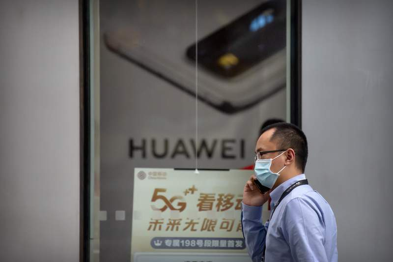 """A man wearing a face mask to protect against the new coronavirus talks on his smartphone as he walks past a Huawei store in Beijing, Wednesday, July 1, 2020. China on Wednesday demanded Washington stop """"oppressing Chinese companies"""" after U.S. regulators declared telecom equipment suppliers Huawei and ZTE to be national security threats. (AP Photo/Mark Schiefelbein)"""