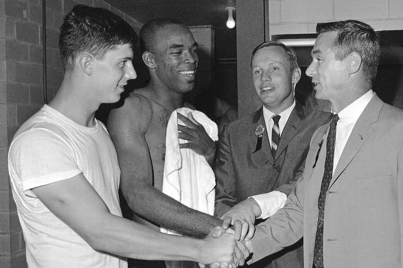 Purdue college football players Mike Phipps, left, and Leroy Keys, second from left, are congratulated by Purdue alumni astronauts Neil Armstrong, second from right, and Eugene Cernan, right, following Purdue's victory over Texas A&M in Dallas, in this Sept. 24, 1967, file photo. Purdue football star Leroy Keyes, a two-time All-American and one of the greatest players in school history, has died. He was 74. Keyes' family said he died at his home in Indiana Thursday morning, April 15, 2021, surrounded by his wife and children. (AP Photo/Ferd Kaufman)