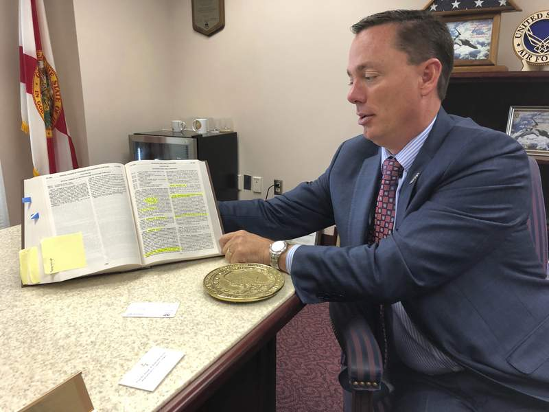 Rep. Tommy Gregory, holds a book of laws that includes antiquated statutes regulating the telegraph industry at his office Wednesday in Tallahassee. Gregory wants lawmakers to repeal these laws that do not apply to today's telecommunication industry. A state House committee on Wednesday agreed unanimously to repeal Chapter 363 of the Florida Statute in its entirety.