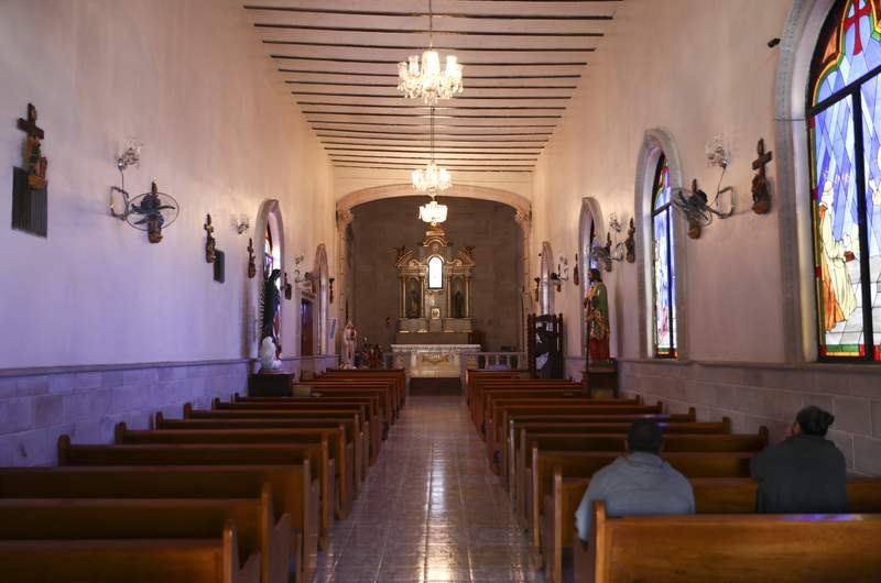 People pray inside the church in Villa Union, Mexico, Tuesday, Dec. 3, 2019. Villa Union bears the scars of the hourslong gun battles Saturday and Sunday. The fight that unfolded between a cartel force estimated at 100 to 150 men and state police left 23 people dead. Many homes and buildings were riddled with bullet holes. (AP Photo/Eduardo Verdugo)