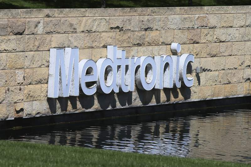 FILE - In this Aug. 29, 2019 file photo, the Medronic logo is reflected in a lake at the company's offices in Fridley, Minn. On Thursday, June 3, 2021, U.S. health regulators warned surgeons to stop implanting an electrical heart pump made by Medtronic due to an electrical problem recently tied to cases of stroke and death. (AP Photo/Jim Mone, File)