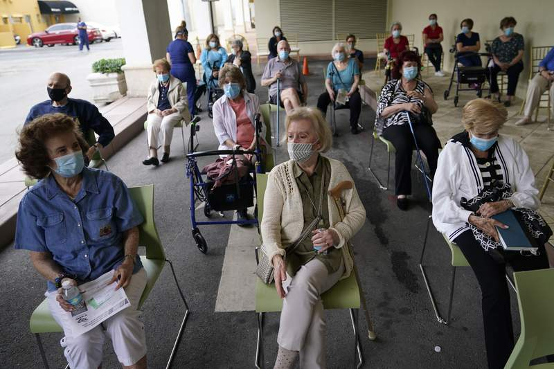 FILE - Residents wait to be cleared after receiving the Pfizer-BioNTech COVID-19 vaccine at The Palace assisted living facility, Tuesday, Jan. 12, 2021, in Coral Gables, Fla. (AP Photo/Lynne Sladky)