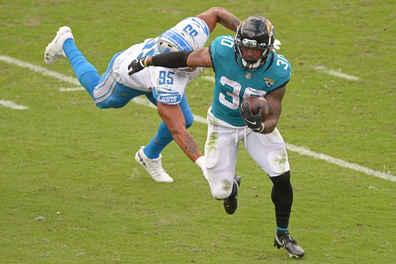 Jaguars running back James Robinson (30) escapes from Detroit Lions defensive end Romeo Okwara (95) during an NFL football game, Sunday, Oct. 18, 2020 in Jacksonville.