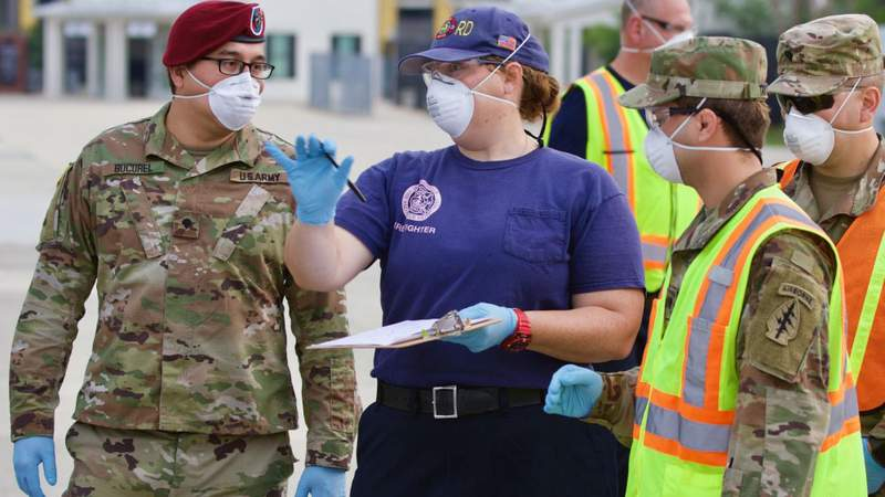Jacksonville Fire & Rescue Department's Amanda Ivory provides direction to Spc. Jeffrey Bucurel (left) as the Florida National Guard began to provide testing at at Jacksonville's COVID-19 community-based testing site at TIAA Bank Field.