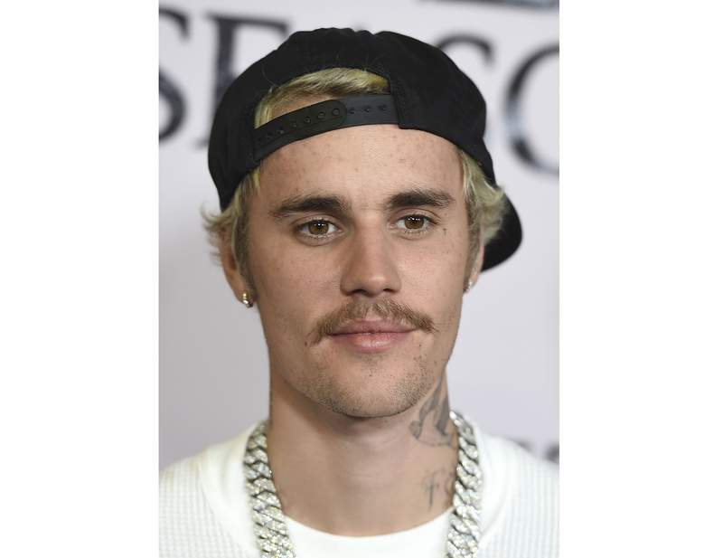 """FILE - In this Jan. 27, 2020, file photo, Justin Bieber arrives at the Los Angeles premiere of """"Justin Bieber: Seasons."""" Justin Bieber leads this years list of nominees at the 2021 MTV Video Music Awards, followed closely by Megan Thee Stallion, Billie Eilish, BTS, Doja Cat, Drake, Giveon, Lil Nas X and first-time nominee Olivia Rodrigo.  Bieber has seven nods, including video of the year and best direction for POPSTAR, artist of the year, best cinematography for Holy and best pop song, best editing and best collaboration for Peaches.  (Photo by Jordan Strauss/Invision/AP, File)"""
