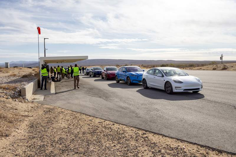 This undated photo by Edmunds shows five electric vehicles at a test track in the Mojave Desert, in California, undergoing testing for maximum range. (Scott Jacobs/Edmunds via AP)