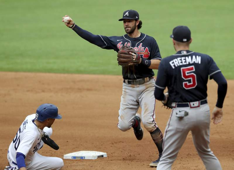 Atlanta Braves shortstop Dansby Swanson, center, is unable to make the throw as Los Angeles Dodgers right fielder Mookie Betts, left, breaks up the double play as Atlanta Braves first baseman Freddie Freeman (5) is shown during the fourth inning in Game 6 Saturday, Oct. 17, 2020, for the best-of-seven National League Championship Series at Globe Life Field in Arlington, Texas. (Curtis Compton/Atlanta Journal-Constitution via AP)