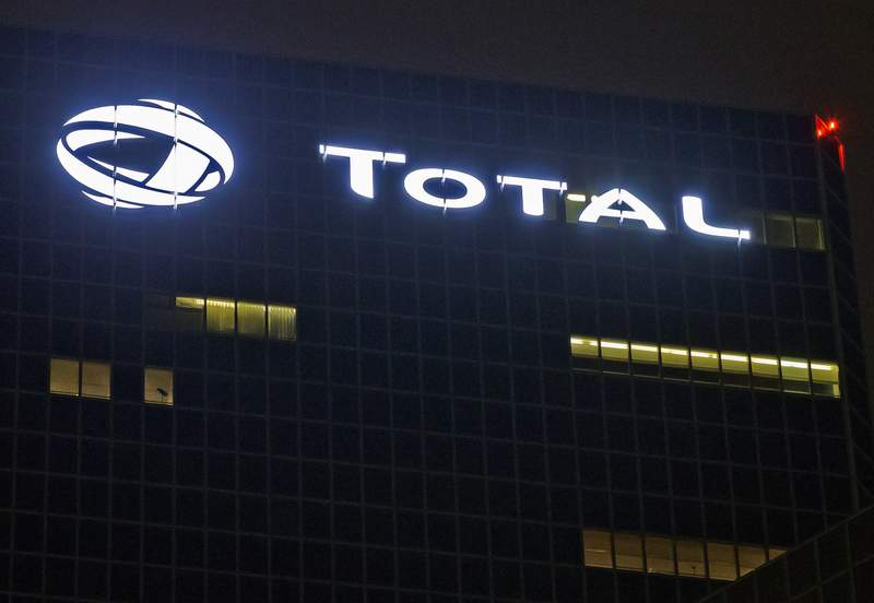 FILE - In this Oct. 12, 2016, file photo, the logo of French oil giant Total SA is pictured at company headquarters in La Defense business district, outside Paris. Shareholders of the French energy company Total SA have voted to suspend payments of dividends to stakeholders in the joint venture company running a gas pipeline in Myanmar, the company says. (AP Photo/Michel Euler, File)