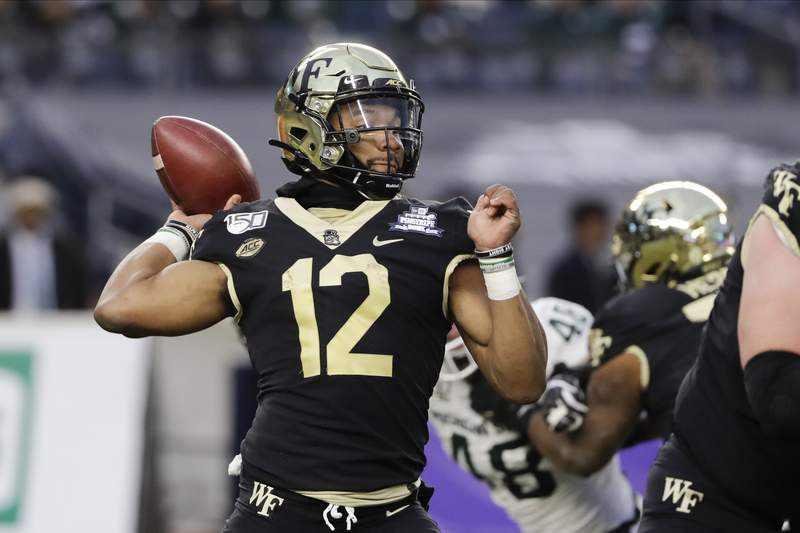 """File-Wake Forest's Jamie Newman (12) throws a pass during the first half of the Pinstripe Bowl NCAA college football game against Michigan State, Friday, Dec. 27, 2019, in New York.  Newman, the Wake Forest transfer who was the projected starting quarterback for No. 4 Georgia, is opting out of the 2020 season to prepare for the 2021 NFL draft. Newman announced his decision on his Twitter account on Wednesday, Sept. 2, 2020. He said he made the decision to skip the season """"after much prayer and discussion with my family.""""(AP Photo/Frank Franklin II, File)"""