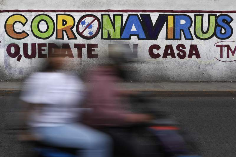 """In this April 28, 2020 photo, a couple rides a motorcycle past a painted sign reading in Spanish """"Coronavirus. Stay Home,"""" in Iztapalapa, Mexico City. Mexico has had extremely limited testing compared with other countries, another factor that experts have said made it difficult for the country to contain the virus. (AP Photo/Rebecca Blackwell)"""