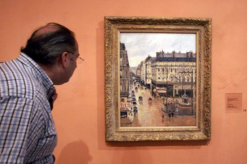 """FILE - This May 12, 2005 file photo shows a visitor viewing the Impressionist painting called """"Rue St.-Honore, Apres-Midi, Effet de Pluie"""" painted in 1897 by Camille Pissarro, on display in the Thyssen-Bornemisza Museum in Madrid. A U.S. federal appeals court on Monday, Aug. 17, 2020 ruled that a priceless Camille Pissarro painting a Jewish woman traded to the Nazis to escape the Holocaust in 1939 may remain the property of the Spanish museum that acquired it in 1992.  (AP Photo/Mariana Eliano, File)"""