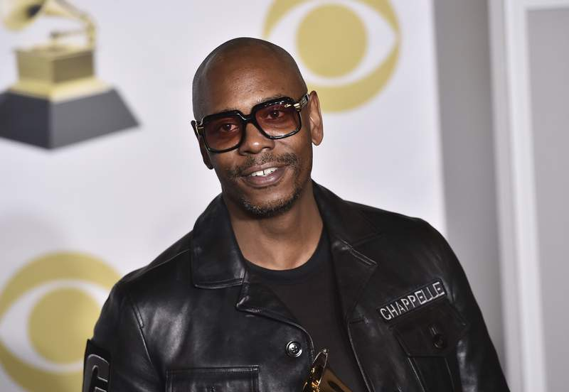 """FILE - In this Jan. 28, 2018 file photo, Dave Chappelle poses in the press room with the best comedy album award for """"The Age of Spin"""" and """"Deep in the Heart of Texas"""" at the 60th annual Grammy Awards in New York. Chappelle celebrated George Floyds life and ripped the media for the way it handled his death in a surprise Netflix special. The special was released Thursday and is streaming free on Netflixs comedy YouTube channel.  (Photo by Charles Sykes/Invision/AP, File)"""
