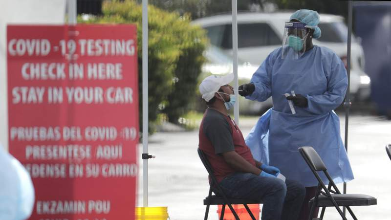 A health care worker administers a COVID-19 test at a site sponsored by Community Heath of South Florida in Homestead.