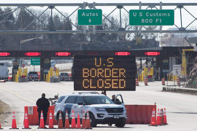 US Customs officers stand beside a sign saying that the US border is closed at the US/Canada border in Lansdowne, Ontario.