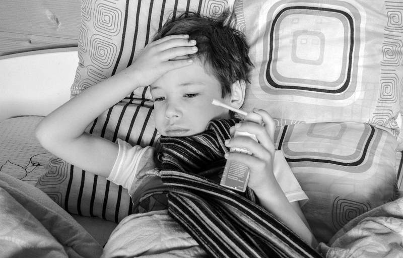 A child lays sick in bed.