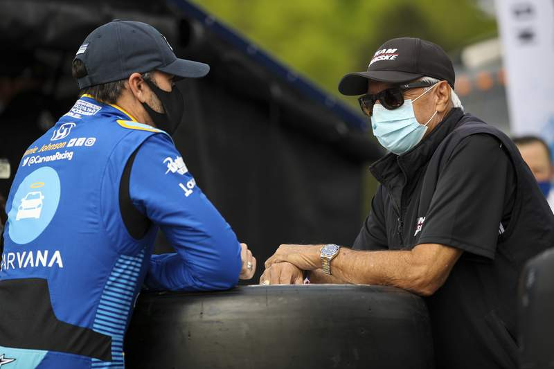 In this image provided by IndyCar, seven-time NASCAR champion Jimmie Johnson,left, speaks to four-time Indianapolis 500 winner Rick Mears before the first IndyCar practice session of the season, Saturday, April 17, 2021 at Barber Motorsports Park in Birmingham, Ala. Johnson will be an IndyCar rookie this season and make his series debut in Sundays opener. Mears was his childhood hero. (Joe Skibinski/IndyCar via AP)