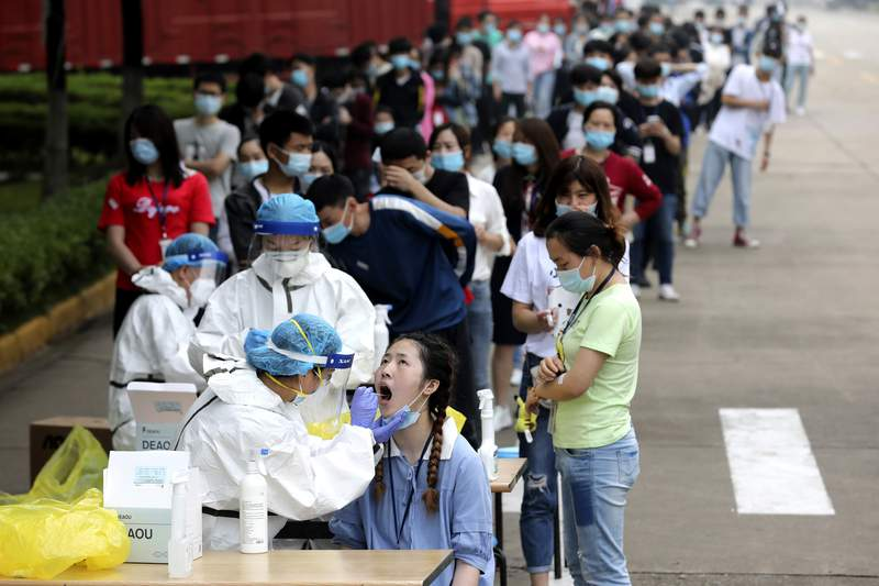 FILE - In this May 15, 2020 file photo, people line up for medical workers to take swabs for the coronavirus test at a large factory in Wuhan in central China's Hubei province. The Chinese city of Wuhan has tested nearly 10-million people for the new coronavirus in an unprecedented 19-day campaign to check an entire city. (Chinatopix Via AP)