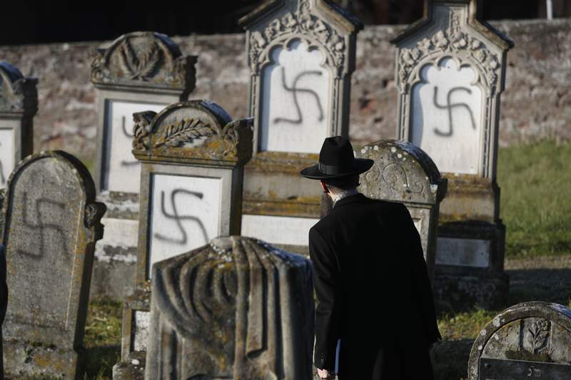 FILE - In this Dec. 4, 2019 file photo, Strasbourg chief Rabbi Harold Abraham Weill looks at vandalized tombs in the Jewish cemetery of Westhoffen, west of the city of Strasbourg, eastern France. Coronavirus lockdowns in 2020 shifted some anti-Semitic hatred online, where conspiracy theories blaming Jews for the pandemics medical and economic devastation abounded, Israeli researchers at Tel Aviv University's Kantor Center for the Study of Contemporary European Jewry in an annual report Wednesday, April 7, 2021. (AP Photo/Jean-Francois Badias, File)