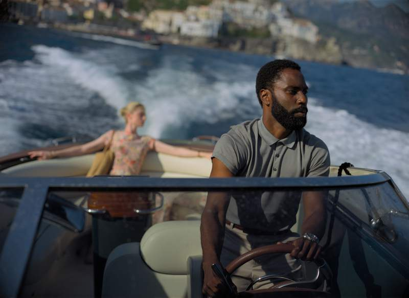 """This image released by Warner Bros. Entertainment shows Elizabeth Debicki, left, and John David Washington in a scene from """"Tenet.""""  As Tenet enters its third week in North American cinemas with barely any new blockbusters on the horizon, U.S. exhibitors are put in a tricky spot. (Melinda Sue Gordon/Warner Bros. Entertainment via AP)"""