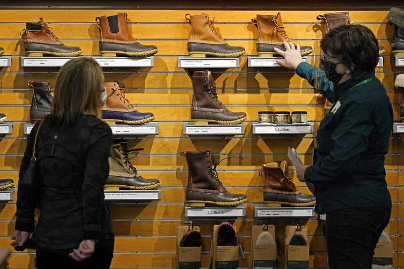 FILE - In this March 18, 2021 file photo, a salesperson helps a customer shopping for Bean Boots at the L.L. Bean flagship retail store in Freeport, Maine.   U.S. consumer spending rebounded sharply in March while incomes soared, reflecting billions of dollars in government support payments aimed at putting the country firmly on the road to recovery.(AP Photo/Robert F. Bukaty, File)