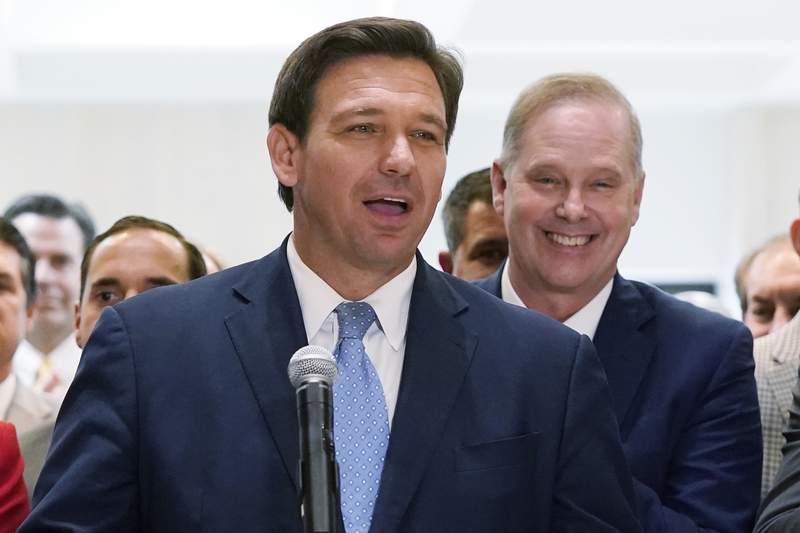 In this April 30, 2021, file photo surrounded by lawmakers, Florida Gov.Ron DeSantis speaks at the end of a legislative session at the Capitol in Tallahassee, Fla. Now that the pandemic appears to be waning and DeSantis is heading into his reelection campaign next year, he has emerged from the political uncertainty as one of the most prominent Republican governors and an early White House front-runner in 2024 among Donald Trump's acolytes if the former president doesn't run again. (AP Photo/Wilfredo Lee, File)